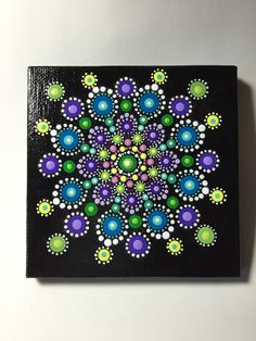 Hand painted with acrylic in yellow, green, purple, and teal. Sprayed with a sealer to protect the colors. Canvas size is 4x4.