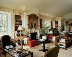 """The addition, a Schinkel-inspired building set apart from the main house, is the ultimate """"bed-sit""""—in Mrs. de la Renta's words—comprised of living room, library, and bedroom. Corinthian pilasters framing the room lend elegance, while the sisal rug protects the space from becoming too precious. Antique textiles from Elinor Merrill, Louis XVI armchairs, and Houghton-inspired mantel mélange to elegant effect."""