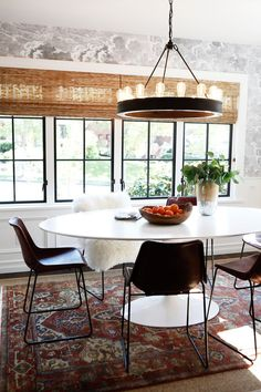 Eclectic dining room design featuring black and white cloud print wallpaper, matchstick roller blinds, a large modern vintage style chandelier, modern white pedestal table and black chairs, and a traditional patterned area rug - Dining Room Ideas & Decor - mydomaine.com