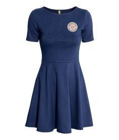 Schwarz. Kurzes Kleid aus festem Jersey mit Applikation auf der Brust. Modell…