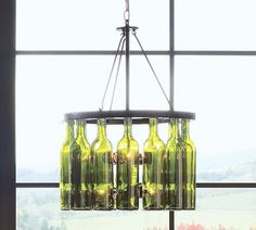 this great idea for wine bottle reuse actually comes from pottery barn and is a chandelier made from an iron ring with reused green glass