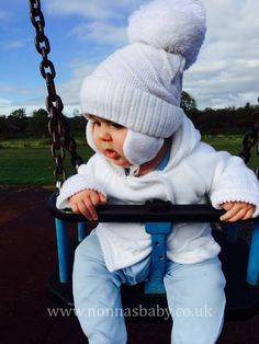 """Carter has fun on the swings! Looks like the cute little man is enjoying himself, and mummy Ashley commented """"Carter is lovely and cozy is his pram coat"""". :-) • Learn more about our range of Pram Coats here: https://nonnasbaby.co.uk/product-category/pram-coats/"""