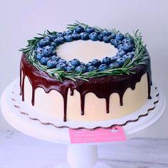 Лимонный торт с сочной клубникой внутри и сливочно-сырным кремом. Оформлен венком из веточек розмарина и ягод голубики, а также аппетитно стекающим темным бельгийским шоколадом. Автор instagram.com/foodbook.cake