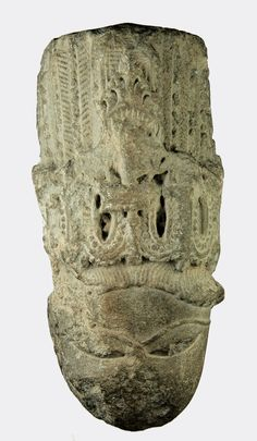 """Indian medieval Hindu deity head: A grey stone sculpture fragment depicting the head of a deity.  India, Pinjore province, c. 11th Century AD  Fragment as shown  Size: 14.3 x 7 cms  Ex. private collection, Cheltenham, UK; acquired late 20th Century.  A mid 20th Century black ink inscription on the back: """"Bassia (Pinjore)"""""""