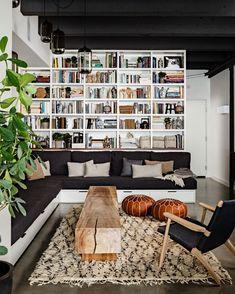 Mid Century Modern living room -- dark floor, clean white modern bookcases, white walls, textured rug.