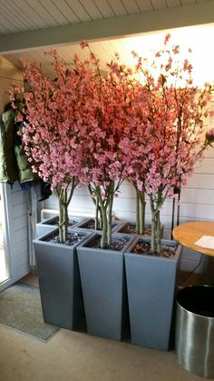 Artificial Pink Blossom Trees set by us in Silver Tapered Planters. These are made individually by us using real wood stems and lifelike flowers.