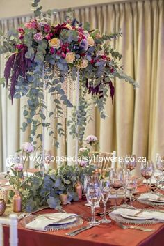 Rich and full table setting on a wine red tablecloth with marsala, pink, peach and lilac flowers. All finished off with rose gold decor detail.