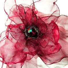 Dramatic organza corsage in shimmering tones of carmine and ruby red...