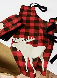 Designed in our studios exclusively for Simons Maison A traditional pattern in an urban lodge style with an accent moose silhouette on large hunter check. Items sold separately. Dimensions Oven mitts: 18 x 32 cm Apron: 70 x 85 cm Potholder: 20 x 20 cm