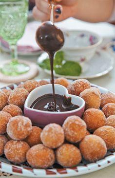 Bolinho de chuva com calda de Brigadeiro Ingredientes da massa (rende 40 unidades): 2 ovos em temperatura ambiente 2 colheres (sopa) de açúcar 1 xícara (chá) de leite 1 fava de baunilha 2 ½ xícaras de farinha de trigo 1 pitada de sal 1 colher (sopa) de fermento em pó Óleo para fritar Açúcar de confeiteiro e canela em pó para polvilhar