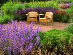 Beds of flowering plants, ornamental grasses and shrubs surround a round brick patio with two Adirondack chairs. The colorful display includes a blend of purples, yellows, violets, pinks and reds.