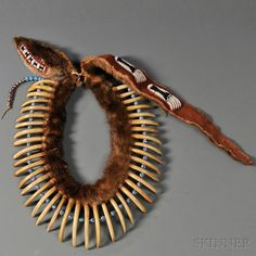 Pawnee-style Bear Claw Necklace,assembled by Milford Chandler (1889-1981) | Constructed with an otter skin painted red beadson the hide side, the head with a black and white beaded strip on red trade cloth, with forty large 19th century grizzly bear claws and large Italian bead spacers; includes a late otter hide drop with six beaded bear paws and two tie-on beaded strips (added by Joseph J. Rivera) | 57,000$ ~ Sold