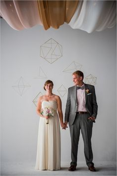 Tri-colour chiffon fabric panels and gold geometric shapes make for a sleek background for photos