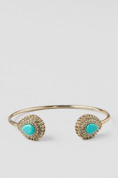Sleek and slender, the Camille Open Bangle Bracelet adds a vintage element to your outfit. The smooth gold band expands into teardrops at either ends that is embellished with a turquoise stone surrounded by rows of crystal rhinestones. Compliment a white dress with the subtle colors of this bracelet.