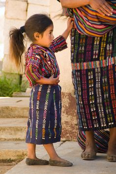An adorable Guatemalan girl dressed in her huipil, the traditional dress of #Guatemala