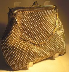 A really pretty and dainty vintage Gold Mesh Whiting and Davis handbag/Purse from the Art Deco period.  Tactile micro mesh which gives the appearance of tiny 'beads' in a gorgeous golden colour with a simple but stylized smooth gold frame and dainty chain link handle.  Peach colour satin lining and 'Whiting and Davis' label inside.  Whiting and Davis were the market leaders in the USA for these beautiful evening bags.