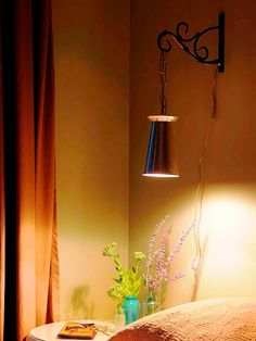 DIY Network has instructions on how to make a wall sconce using an old vase and a garden hanger.