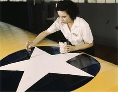 Grace Weaver paints an insignia on an airplane wing. Photographed by Howard R. Hallem in August 1942