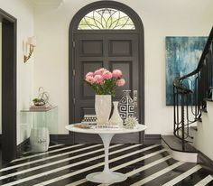 Put white round end table with vase and flowers above end table in entry way with black front door