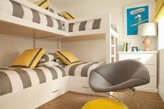 White boys' bunk room with yellow and gray accents features L shaped bunk beds…