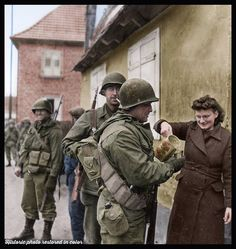 American Soldiers from the 2nd Battalion, 314th Infantry Regiment-79th Infantry Division receive wine from French civilians during a lull in the fighting around Drusenheim, France on January 6, 1945.
