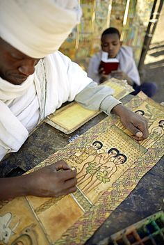 Priest painting and writing biblical scenes in Geez on goatskin, Lalibela, Ethiopia