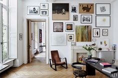 loving the salon hang or gallery hang of art and the amazing herringbone floorboards and huge windows of this Parisian apartment