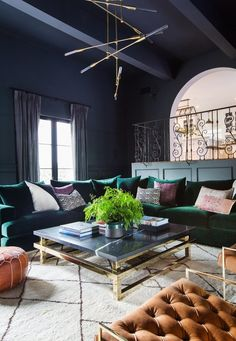 Shay Mitchell's moody living room with gray walls, a gold chandelier, and a velvet green sectional