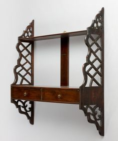 A set of Chippendale period mahogany hanging shelves with pierced fretwork sides and retaining its original axehead handles. Circa 1765.   Ref: 2284