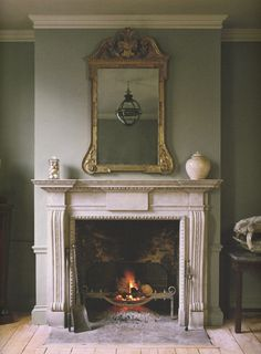 ~Jamb - The Chesham chimneypiece in distressed Portland stone with the Arts and Crafts fire basket and Stockton fire irons. A small Original Globe is reflected in the mirror. Vintage Fireplace, Home Fireplace, Living Room With Fireplace, Fireplace Surrounds, Fireplace Design, Antique Fireplace Mantels, Fireplace Ideas, Antique Mantel, Stone Fireplace Mantel