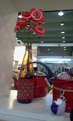 Flores de botão na garrafa reciclada com capinha de tecido