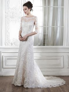 Maggie Sottero Wedding Dresses, Spring 2015. The color is ivory over nude.A dramatic illusion lace back and illusion sleeves adorn this hand-embellished sheath gown, glimmering with metallic lace appliques and embroidered with Swarovski crystals drifting from shoulder to floor-skimming hem. A delicate scalloped hemline completes the look. Finished with pearl button over zipper back closure.