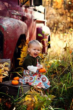 sweet little girl with old truck and lil' pumpkins