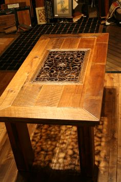 Custom reclaimed barnwood table with a cast iron grate in the center. L! O! V! E!