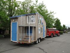 Tiny House with an upper story balcony pulled by a fire truck