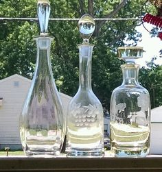 Here we have three vintage mid century or earlier blown glass liquor decanters probably from Romania or Hungary or there abouts. The one on the left is a Toscany I believe it's iridescent with an optic rib. The middle one is a bell shaped decanter and has a nice grape pattern etched very nice. Lastly the one on the right is the finest of them all older to I believe. It has an outstanding floral etching, & is also the heaviest of the three with a massive flat knob stopper. The tallest Toscany…