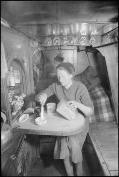 Mrs March prepares bread and butter on a pull-down table in the tiny cabin of the 'HEATHER BELL'. Behind her, horse brasses, cushions and a small vase of flowers brighten up the wooden barge interior. Barge Boat, Canal Barge, Barge Interior, Rv Interior, Interior Ideas, Canal Boat Interior, Boating License, Narrowboat Interiors, Boating Tips