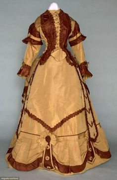 "Augusta Auctions - Silk Faille bustle dress, 1868-72; 3 piece, peplum bodice, bell skirt & bustle overskirt; ruched bands, fringed bows, bodice lined in muslin, glazed cotton & buckram skirt lining; bust: 35""; waist: 23.5"", very good condition."