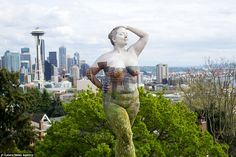 One hand on her hip, and the other placed on her head, a performer looks serene as her legs merge into the tree backdrop of the Seattle skyline