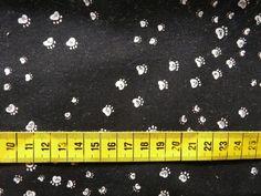 Katoenen stof met een print van witte kleine (honden)pootafdrukjes op een zwarte achtergrond