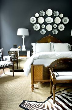 Courtney Giles: a bold bedroom design with black walls, antique wood bed and bench, mirrored modern nightstands, alabaster lamps, sisal rug, decorative antique wall plates and black and white textiles.