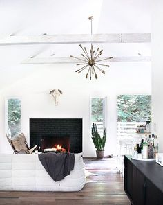 High ceilings, gray washed beans, black brick fireplace surround