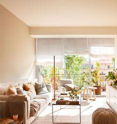 Salón con gran ventanal, sofá arrimado a la pared, butaca y mueble bajo