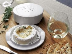 Pure white stoneware brie baker with integrated handles has a ventilated lid to release steam for delicious Brie-based appetizers, potluck and buffet dishes. Bake, serve and store in one dish. Includes recipe for apple walnut topping.