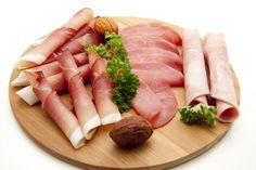 Lunchplank. Het hoeft allemaal niet zo ingewikkeld. Gewoon een mooi houten bord met daarop een paar plakken en rolletjes van rauwe- en gekookte ham en rookvlees. Een paar walnoten en peterselie als garnering.