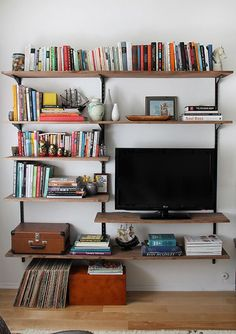 tv with books on stained wood shelves hung with shelving standards