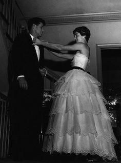 Jackie Kennedy helping her husband, President of the United States of America, fix his bowtie before going to a reception. ca. 1950's