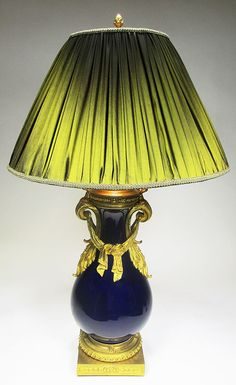 A Very Fine and Large French Napoleon III Ormolu Mounted Cobalt-Blue Urn Lamp, probably by Sevres (Now electrified). The ovoid porcelain vase surmounted with floral handles with swags and ribbons, raised on a square plinth with detailed chasing. Circa: 1880