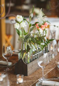 Lines of bloom-filled bottles in rustic wooden boxes // Don Mears Photography