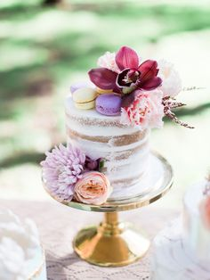 Mini semi naked wedding cake on gold stand with orchid, tulip and macaron topper | We Are Origami Photography